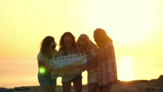 Tourist girls looking at guidebook. Woman tourist looking at map at seashore. Girls silhouettes talking about tomorrow journey. Human silhouettes on sunset background. Female tourist looking map