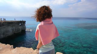 Tranquil woman enjoy rocky sea landscape. Tourist woman relaxing on sea shore at summer vacation. Thoughtful woman on rocky cliff at holiday trip. Alone woman looking on rocky water landscape