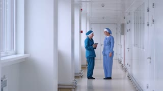 Two female workers talking in white corridor. Pharmaceutical workers talking in laboratory corridor. Researchers talking in white corridor. Factory women talking with tablet in hand