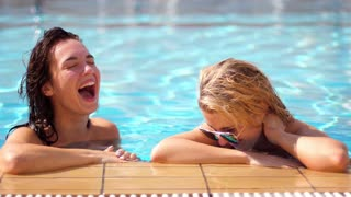 Two girlfriends laugh in pool. Pretty girls spending time on vacations. Enjoying summer. Lifestyle concept. Girls in excellent mood bathing in pool on vacations. Women relaxing