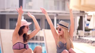 Two girls dancing sitting on chaise longue and having fun on vacation. Stylish women enjoying vacation. Happy girls in stylish hats and sunglasses smiling. Dancing girls have fun at summer pool