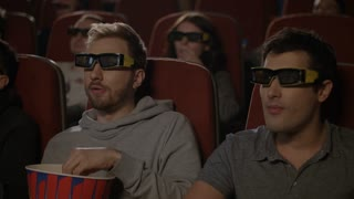 Two guys in 3d glasses watching movie. Men smiling and chewing popcorn. Friends watching 3d movie in cinema. 3d cinema entertainment concept. People enjoy multiplex movie