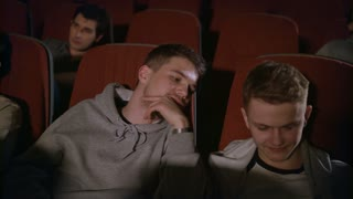 Two guys looking smartphone in cinema. Male friends having fun with phone at movie theatre in slow motion