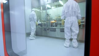 Two pharmaceutical manufacturing workers in white uniform control production process. Scientists working in laboratory. Medicine production equipment. Factory employee control pharma production