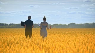 Two researchers going away in wheat field in sunlight. Male and female agronomist walk away in harvest field. Agro scientists working in field at summer