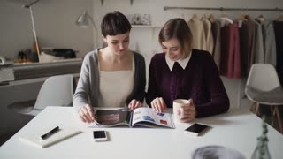Two sisters together reading woman magazine. Woman looking fashion magazine sitting at table in home workshop. Creative woman leisure time