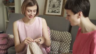Two woman friends looking on knitting yarn. Two woman friends knitting yarn wool in home room