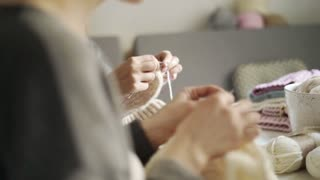 Two woman knitting needles wool clothes. Close up women together knitting needles woolen clothes in home. Woman leisure activity