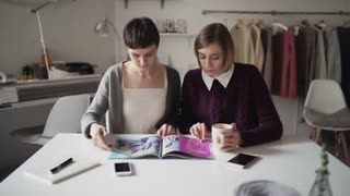 Two woman spend leisure together and reading fashion magazine. Woman looking design magazine sitting at table in textile workshop. Woman leisure time