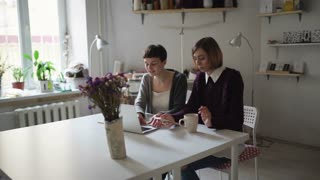 Two woman students at table using notebook for online learning. Young woman looking on screen laptop in home. Women in cozy studio chatting online