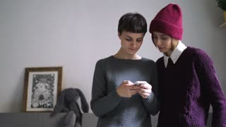 Two young woman looking photo at mobile phone. Female friends using smart phone in home interior. Woman using smartphone