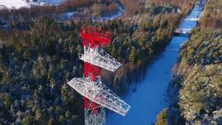 View from above electricity pylon on background winter landscape in forest. High voltage electricity pylon. Transmission tower in forest. Power engineering