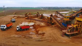 View from above mining conveyor working on sand mine. Mining conveyor pour sand in dumper truck. Mining equipment on industrial park. Aerial view of mining machinery on sand quarry