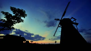 Village sunrise timelapse. Morning sunrise at rural landscape. Rural windmill silhouette. Morning sunlight in village. Morning sunshine landscape. Sunrise sky and clouds. Sunrise landscape
