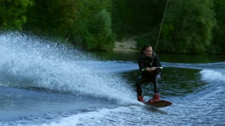 Wake board rider jumping high over water. Dangerous trick over river. Extreme water sports. Action time in summer. Wakeboarder making tricks. Extreme wakeboarding sport. Wake surfing rider on water