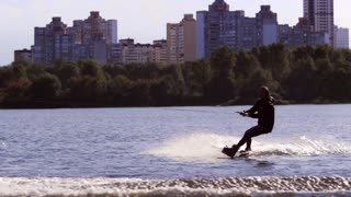 Wake board rider jumping on river waves. Extreme lifestyle. Man doing wakeboarding tricks on city river. Guy enjoy extreme on wakeboarding boat