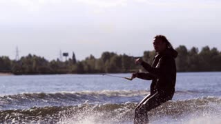 Wake boarding rider enjoy training. Rider surfing between waves on water board in slow motion. Courageous man jumping over wave. Extreme hobby. Surfer making trick on wakeboard. Extreme life style