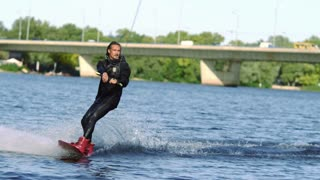 Wakeboarder jumping high above water. Professional sportsman making trick aver water surface. Athlete satisfied with his action. Young manwakeboarding on lake. Water sports. Extreme lifestyle
