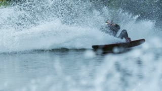 Wakeboarder making tricks on waves during movement in slow motion. Joyful man riding wakeboard in water splash. Athlete water skiing and have fun. Extreme water sports