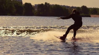 Wakeboarder surfing on river behind motorboat. Extreme wakeboarding at sunset. Wakeboard rider moving fast in splashes of water at golden sunset. Extreme water sport