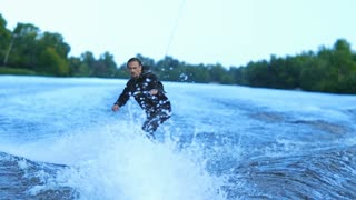 Wakeboarder waterskiing on river behind boat. Summer river wakeboarding. Extreme mode of rest. Sportsman waterskiing giving signals to motorboat driver. Wake boarding rider