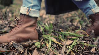 Walking legs in brown shoes side view. Walking feet in brown leather boots and blue jeans along foliage. Close up foot in jeans and boots stepping on fallen autumnal foliage in forest