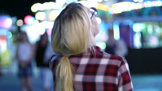 Walking woman back in amusement park. Back view of walking girl enjoy night park. Blondy woman going at park amusement. Female tourist enjoy evening light city. Night walk