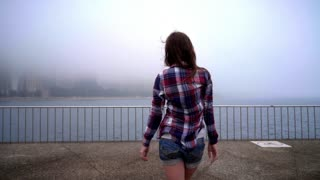 Walking woman looking on ocean city fog. Back view of woman coming to embankment. Young woman walking out of ocean in foggy weather. Woman going to sea city. Loneliness in city