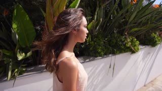 Walking woman outdoor. Close up of walking girl face in tropical city. Luxury woman going in modern city in slow motion. Beautiful girl enjoy city walk