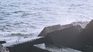Water rocks. Rocks in water. Sea waves crashing on rocks. Water crashing on breaker blocks. Breakwaters on ocean shore. Crashing waves. Water tide on rock shore