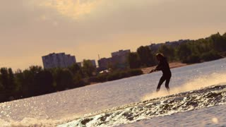 Water skier moving fast in splashes of water at sunset. Extreme watersports. Man wake boarding on city river at sunset. Free lifestyle. Rider wakeboarding on lake behind boat. Adrenaline sport