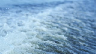 Water splashes on river surface in slow motion. Trail on water surface behind of fast moving motor boat. Water wave background
