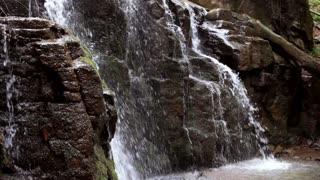 Waterfall in rocky mountain. Water flowing down in rocky path. Stone water stream in mountain. Waterfall rocks landscape