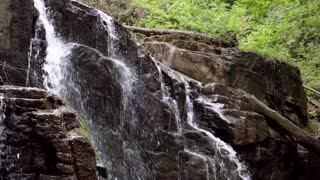 Waterfall on rocky mountain. Water stream quickly fall down and create white bubbling foam. Stone waterfall in mountain forest