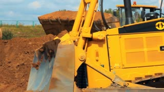 Wheel loader and excavator working on construction site. Heavy machinery in mining quarry. Wheel bulldozer moving soil in scoop. Close up of excavator bucket working on building territory