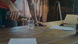 Whiskey from bottle pouring in glass in slow motion. Close up of male hand pouring whisky in glassful on table. Whiskey glass on wooden table. Jack daniels splash