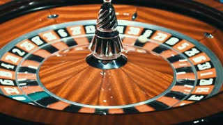 White ball stopped in rotating casino roulette. Close up wooden roulette wheel. Classic gambling game in traditional casino. Wheel of fortune concept
