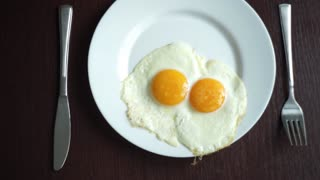 White plate with fried egg on wooden table. Serving breakfast eggs. Fried eggs on plate. Close up white porcelain plate with breakfast eggs fried. Traditional breakfast on white plate