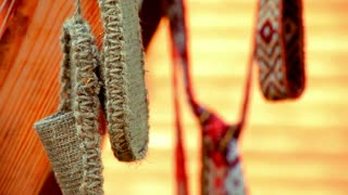 Wicker vintage bast shoes hanging on street. Traditional old bast shoes and ribbons with ethnic pattern in background. Close up national woven slavic basketry shoes. Slavic country wicker shoes