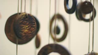 Wind swinging coins slowly. Closeup of antique Chinese coins hanged indoors. Feng shui amulet for lucky and protection. Wind chimes from coins