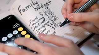 Woman calculate family budget on calculator and writing in notebook. Family budget calculation. Home accounting and domestic finances managing. Family finance concept