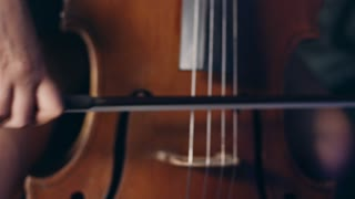 Woman hand playing violoncello with cello bow. Close up of female hand playing cello with cello bow. Cello playing music background. Female musician playing violoncello