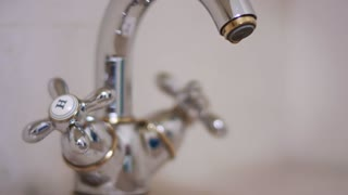 Woman hand pouring water into glass from water faucet on kitchen. Close up female hand pouring cold water from kitchen tap