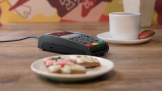 Woman hand swipe credit card in payment terminal. Woman paying by credit card in cafe. Pos terminal payment for order in cafe. Girl buy sweet cookies in cafe