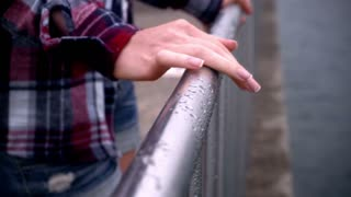 Woman hands on steel fence. Elegant woman hands on railing, wipe the water drops after rain. Close up of woman manicured hands on metalic railing with water drops