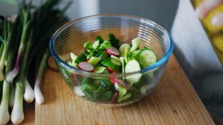 Woman hands pouring olive oil into glass bowl with fresh spring salad. Close up cooking woman hands. Natural vegetarian salad with onion, cucumber and radishes. Healthy lifestyle with organic food