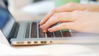 Woman hands typing keyboard of laptop computer in office. Close up of business woman hands working on laptop at office workplace. Female hands using notebook computer. Office worker typing on keyboard