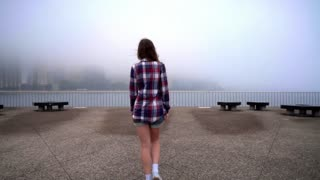 Woman in casual shirt going to fence steel nea sea. Back view of woman looking on fog sea. Woman looking on fog city. Back woman standing on embankment. Back view girl looking fog ocean