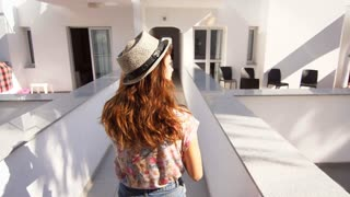 Woman in hat walking in resort hotel. Back view of walking girl in hat showing finger in white building. Female tourist showing hotel. Brunette girl showing hotel