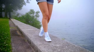 Woman legs walking on parapet near sea coast. Female legs on beach sea. Close up of woman feet walking. Beautiful legs woman going on border sea